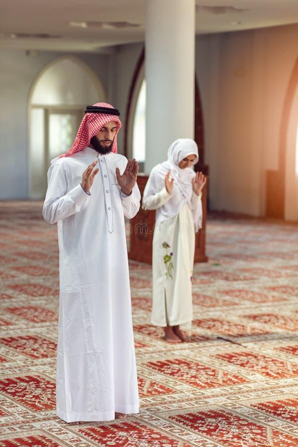 Мусульманские моля человек и женщина в мечети стоковая фотография rf