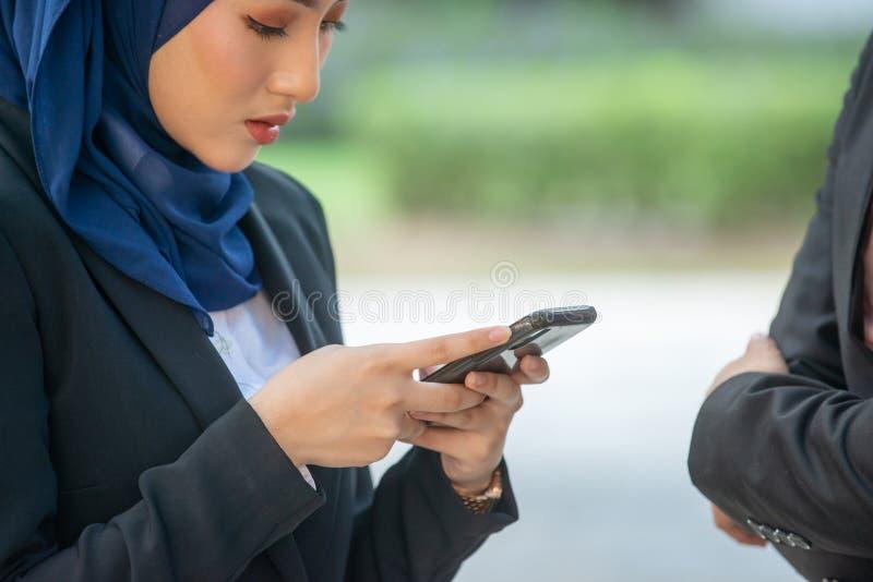 Мусульманские пары на их смартфоне Получивший SMS и заканчивающ связь их социальным средствам массовой информации стоковое фото