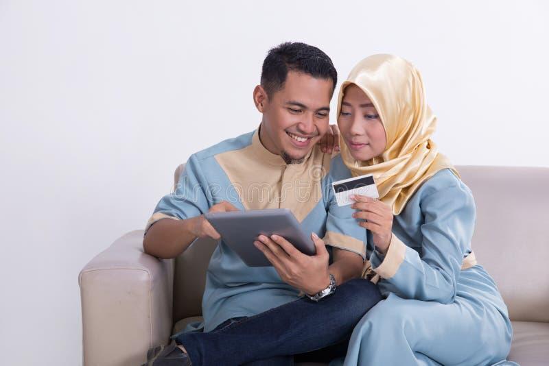 Мусульманские пары на кресле с таблеткой стоковое изображение rf