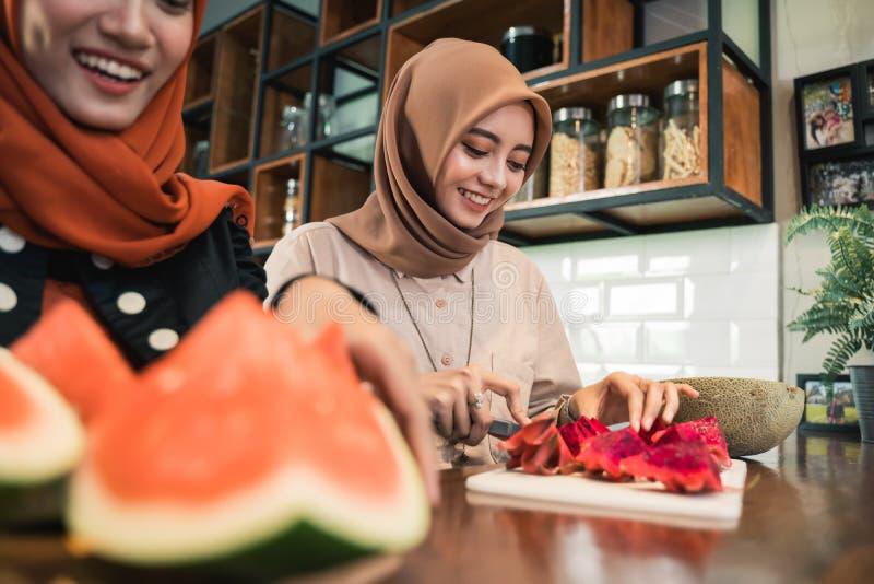 Мусульманский друг женщины подготавливая некоторый коктейль десерта плода стоковая фотография rf
