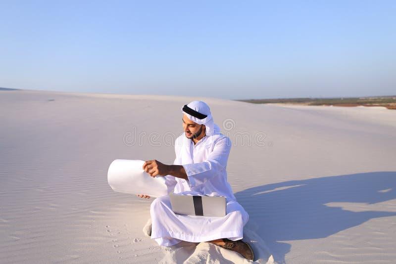 Мусульманский мужской архитектор сидя с компьтер-книжкой на песке в пустыне на h стоковые фотографии rf