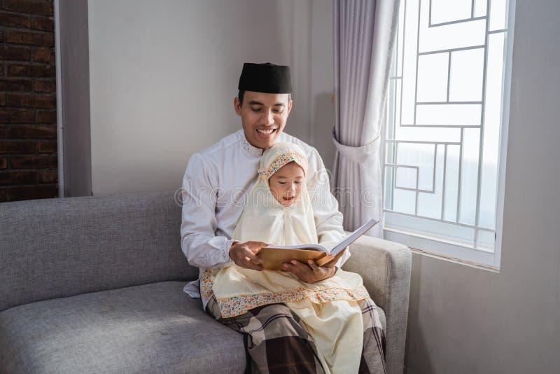 Мусульманский отец прочитал Коран с его дочерью стоковые фото