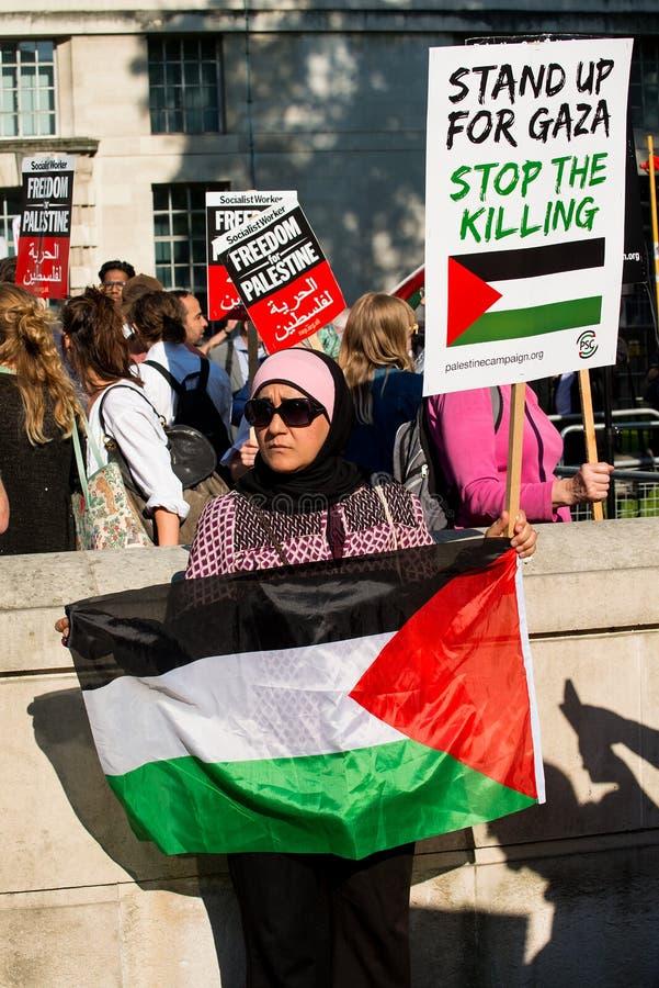 Мусульманский протестующий женщины с плакатом на Газа: Остановите ралли бойни в Уайтхолле, Лондоне, Великобритании стоковое изображение