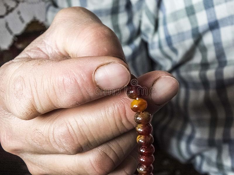 Мусульманский человек который привлекает хваление, мусульманин который поклоняется мусульманский человек вытягивая розарий стоковое изображение