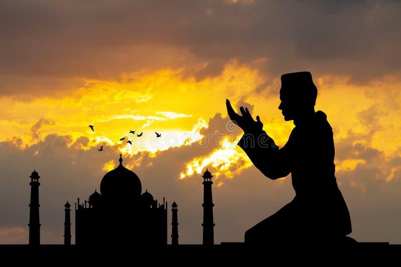 Мусульманский человек молит к Тадж-Махалу стоковое изображение