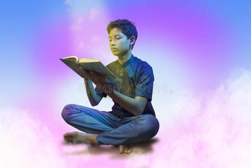 """Мусульманский человек сидя положив ногу на ногу поднял его руки держа и читая святое Qur """" стоковое изображение rf"""