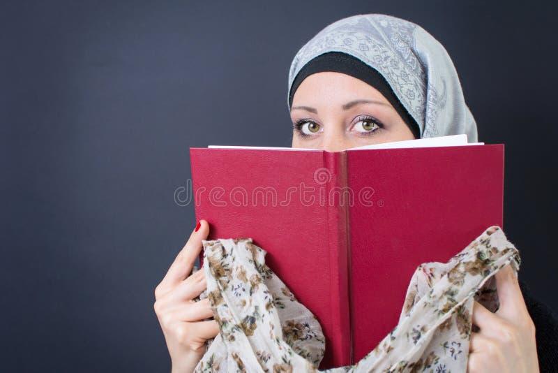 Мусульманская женщина держа книгу стоковое фото