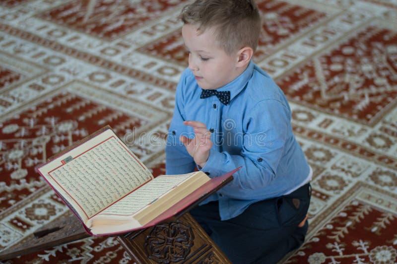 Мусульманский ребенок читая Koran стоковое фото