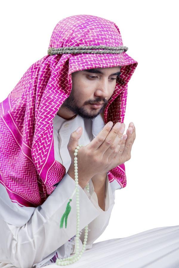 Мусульманский человек молит к Аллаху на студии стоковые изображения