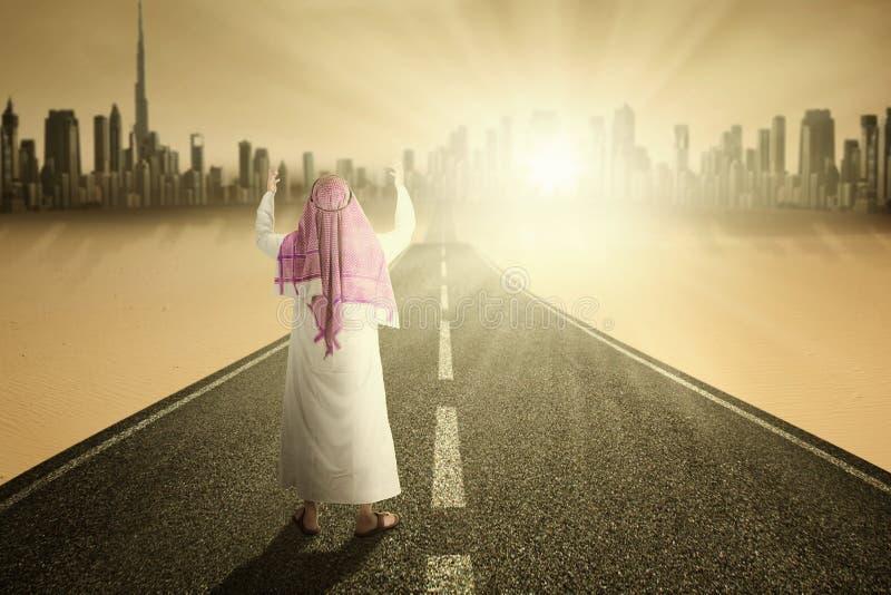 Мусульманский человек молит на дороге стоковое изображение