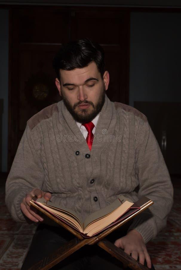 Мусульманский человек читая Koran в мечети стоковая фотография rf