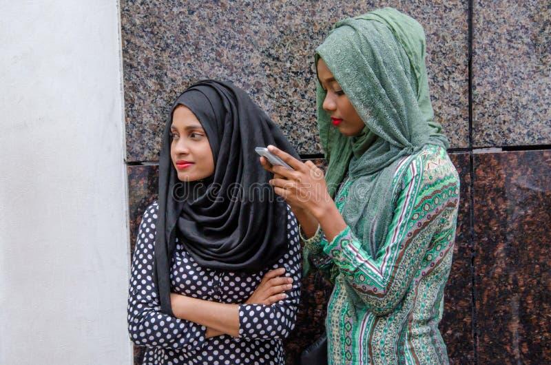 2 мусульманских мальдивских девушки на улице используя мобильный телефон стоковое изображение rf