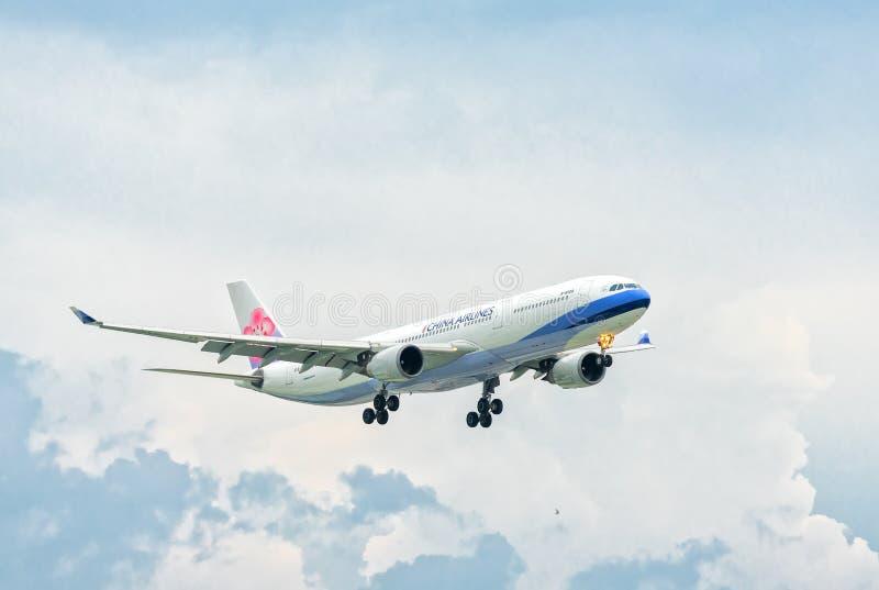 Муха груза China Airlines Боинга 747 над городскими местностями с радугой за небом подготавливает приземляясь международный аэроп стоковое изображение