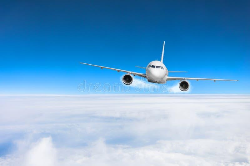 Муха самолета над облаками и ` s земли отделывают поверхность под голубым небом стоковая фотография rf