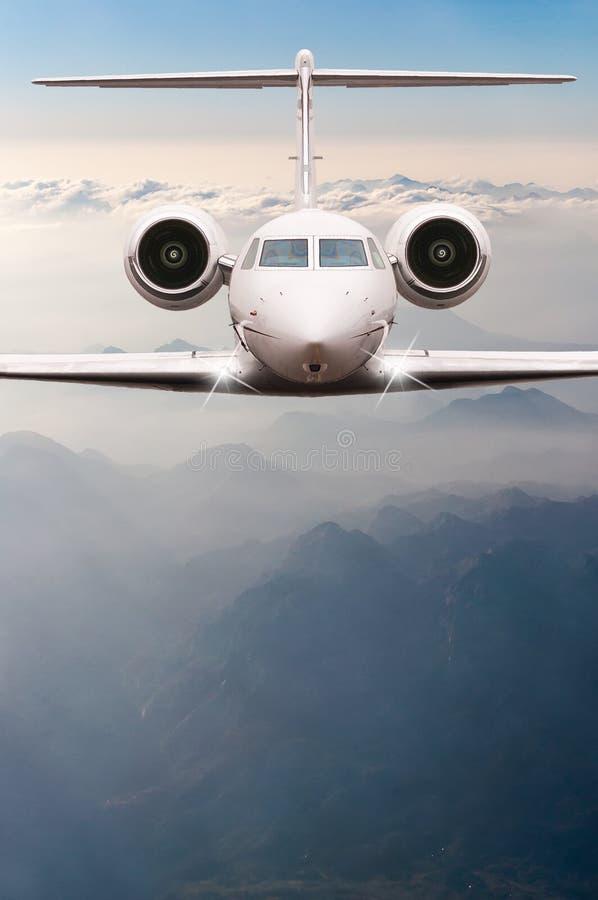 Муха самолета над облаками и горой Альпов на заходе солнца Вид спереди большого воздушного судна пассажира или груза, двигателя д стоковая фотография