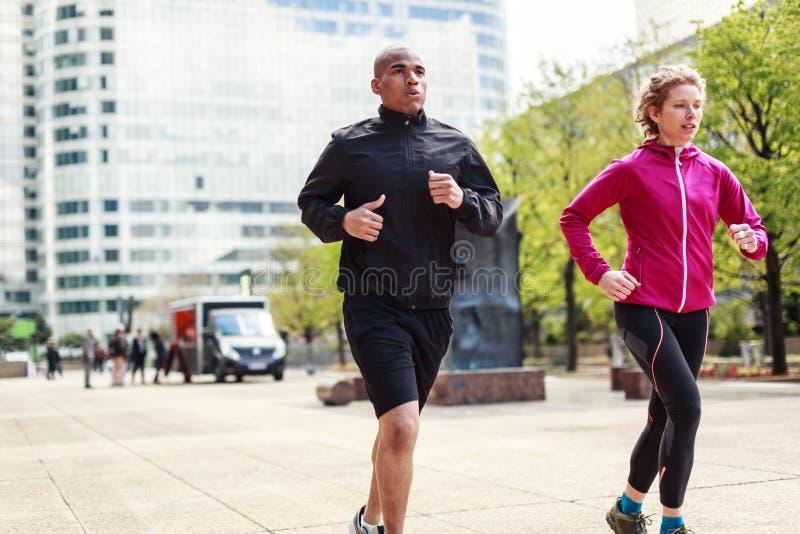 Мульти-этнические пары Jogging в городских условиях стоковые изображения