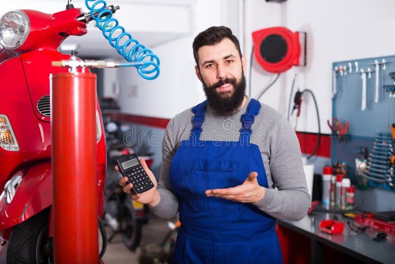 Мульти-этнический парень расчетливая сумма для ремонтировать мотоцикл стоковая фотография