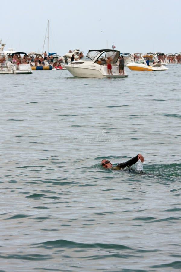 Мыжской пловец делает Backstroke между Partying шлюпки стоковые изображения