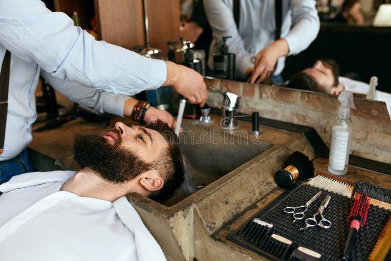 Мытье волос Волосы ` s человека парикмахера моя в салоне красоты стоковое изображение