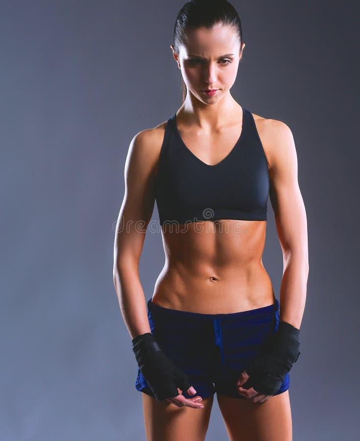 Мышечная молодая женщина представляя в sportswear против черной предпосылки стоковая фотография