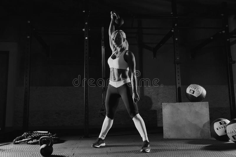Мышечная молодая женщина фитнеса поднимая вес в спортзале стоковые изображения rf