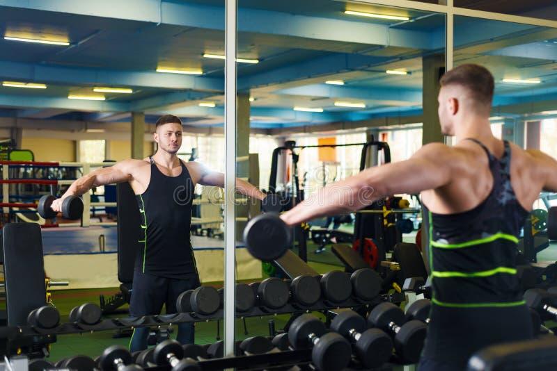 Мышечная тренировка человека в спортзале молодой парень комплектует вверх гантель около зеркала стоковые фото