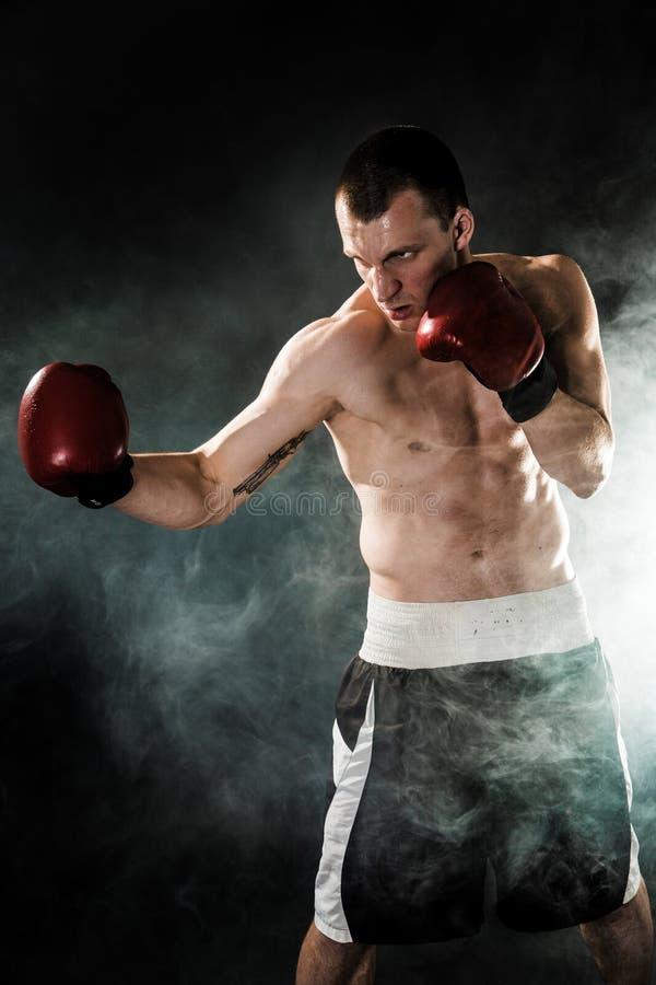 Мышечное kickbox или muay тайский боец пробивая в дыме стоковые изображения rf