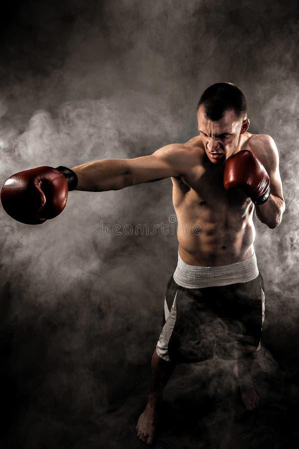 Мышечное kickbox или muay тайский боец пробивая в дыме стоковые изображения