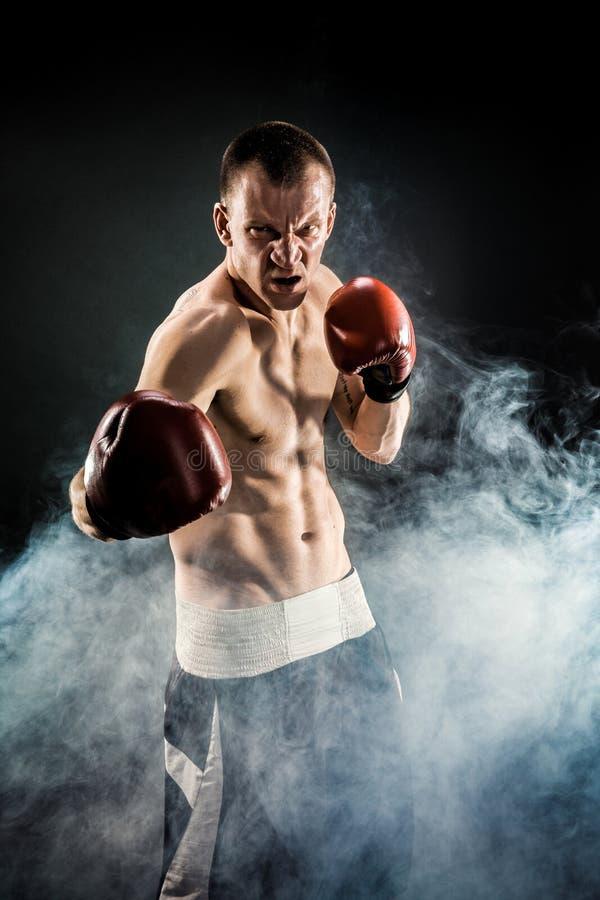 Мышечное kickbox или muay тайский боец пробивая в дыме стоковая фотография