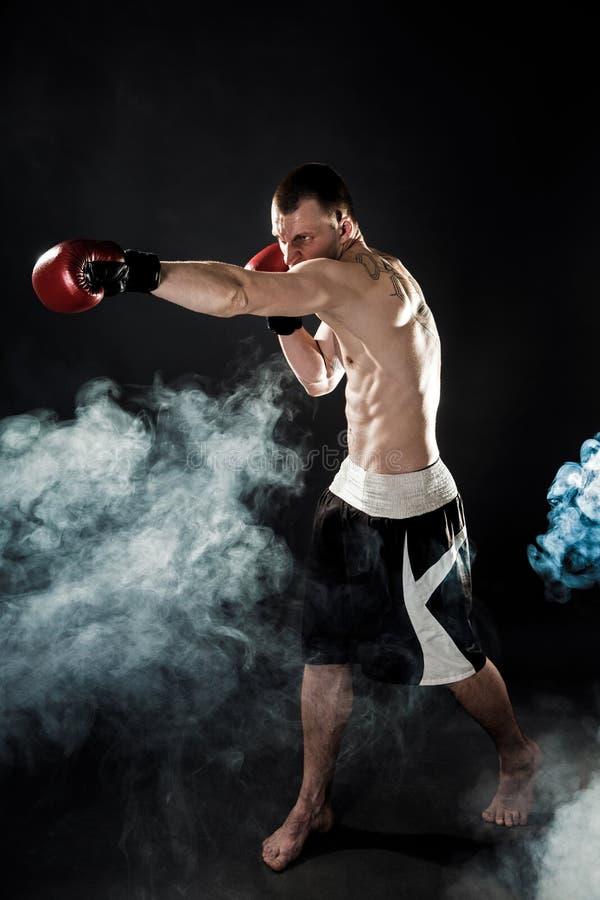 Мышечное kickbox или muay тайский боец пробивая в дыме стоковые фотографии rf