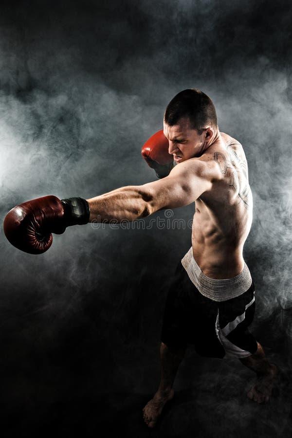 Мышечное kickbox или muay тайский боец пробивая в дыме стоковое фото rf