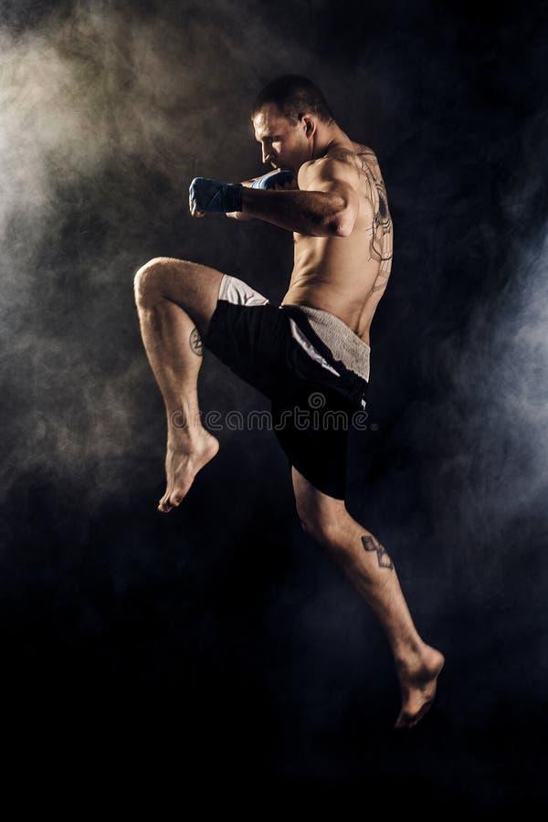 Мышечное kickbox или muay тайский боец пробивая в скачке o стоковая фотография rf