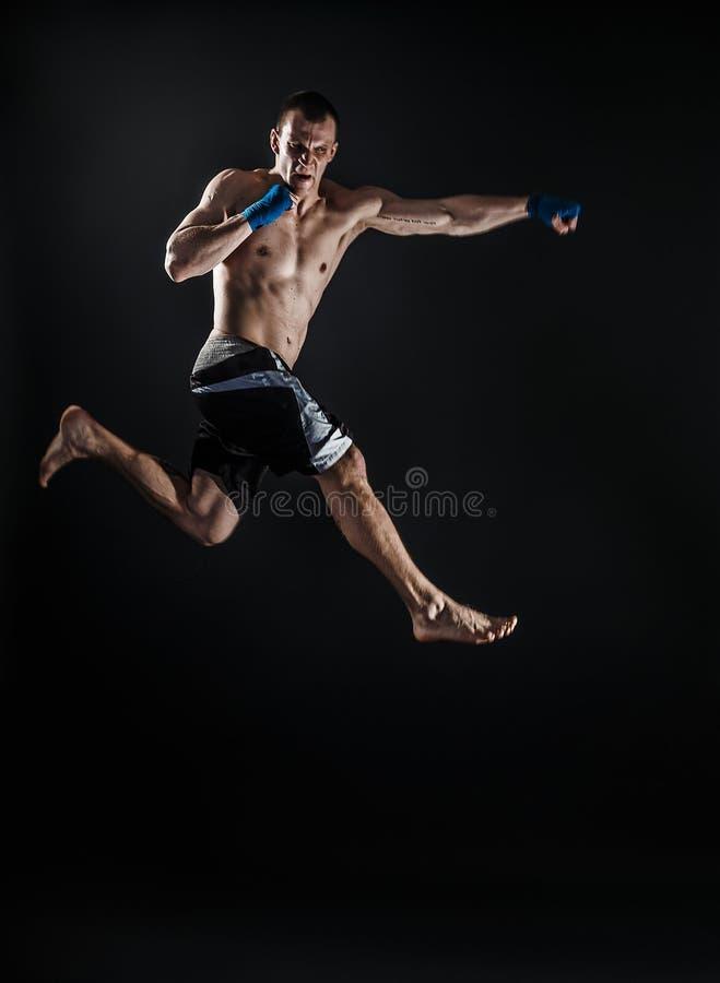 Мышечное kickbox или muay тайский боец пробивая в скачке o стоковое фото rf