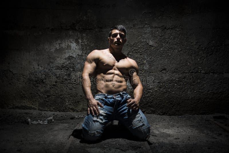 Мышечный без рубашки молодой человек на его коленях с светом над головой стоковая фотография