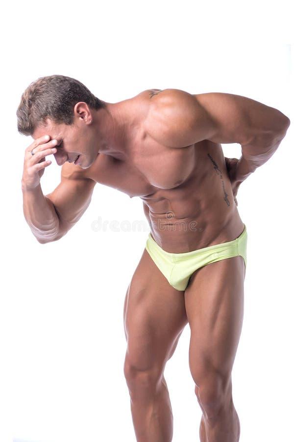 Мышечный красивый человек держа его назад в боли стоковые изображения rf