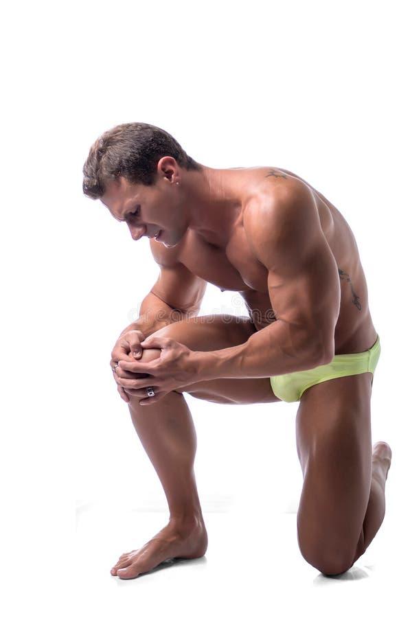 Мышечный красивый человек держа его ногу и колено внутри стоковое фото