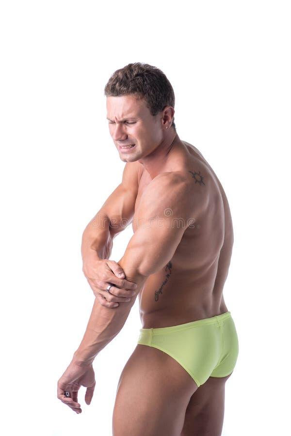 Мышечный красивый человек держа его локоть и руку внутри стоковое изображение rf