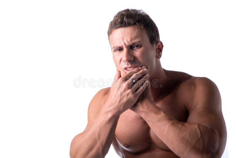 Мышечный красивый человек держа его челюсть для стоковые фото