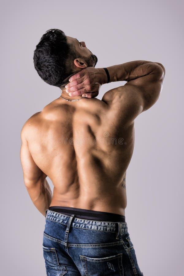 Мышечный красивый человек держа его шею в боли стоковые изображения