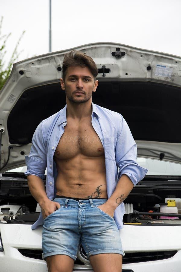 Мышечный мачо человек с его автомобилем стоковое изображение