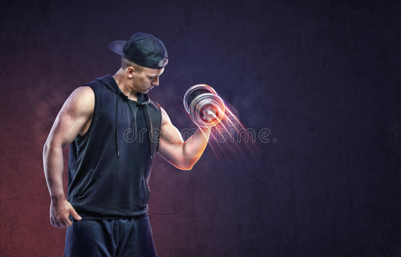 Мышечный молодой парень поднимая гантель к тренировке его бицепса стоковая фотография rf