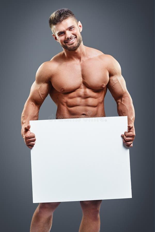 Мышечный молодой человек держа пустой белый плакат стоковая фотография