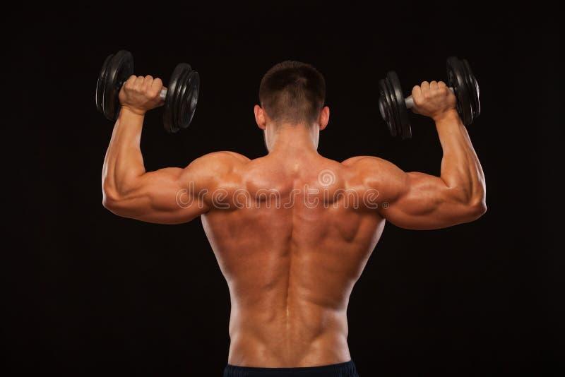 Мышечный мужской модельный культурист делая тренировки при гантели, повернутые назад Изолированный на черной предпосылке с Copysp стоковое фото
