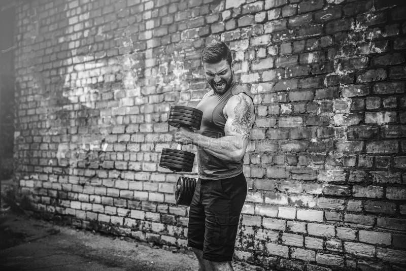 Мышечный парень делая тренировки с гантелью против кирпичной стены стоковая фотография rf