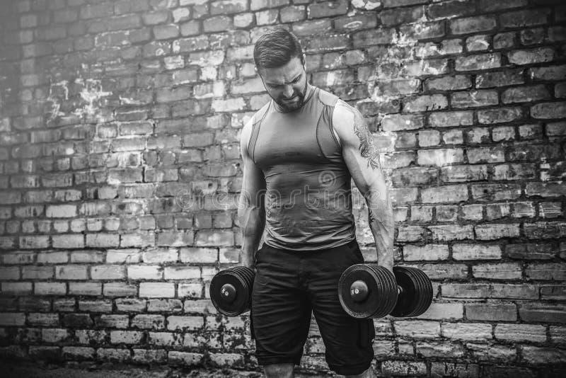 Мышечный парень делая тренировки с гантелью против кирпичной стены стоковое фото