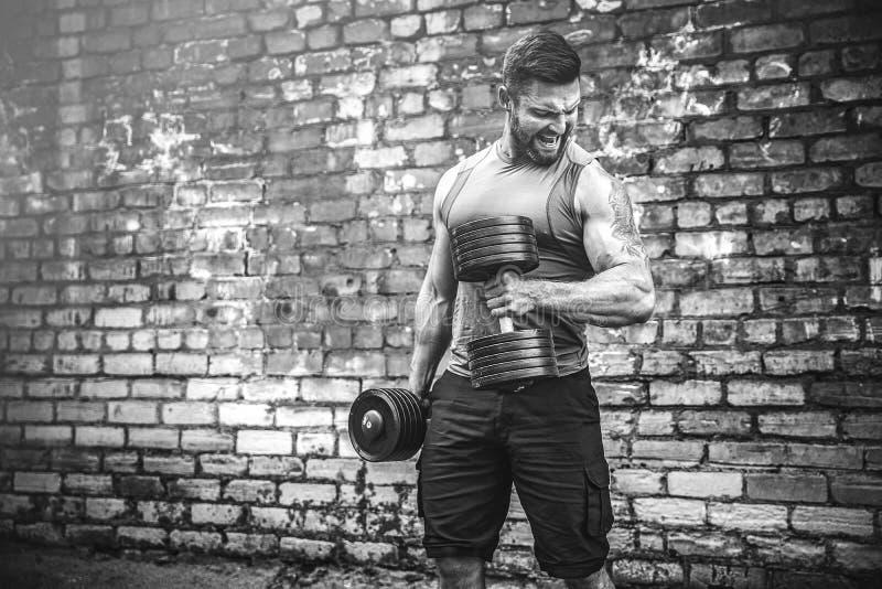 Мышечный парень делая тренировки с гантелью против кирпичной стены стоковые фотографии rf