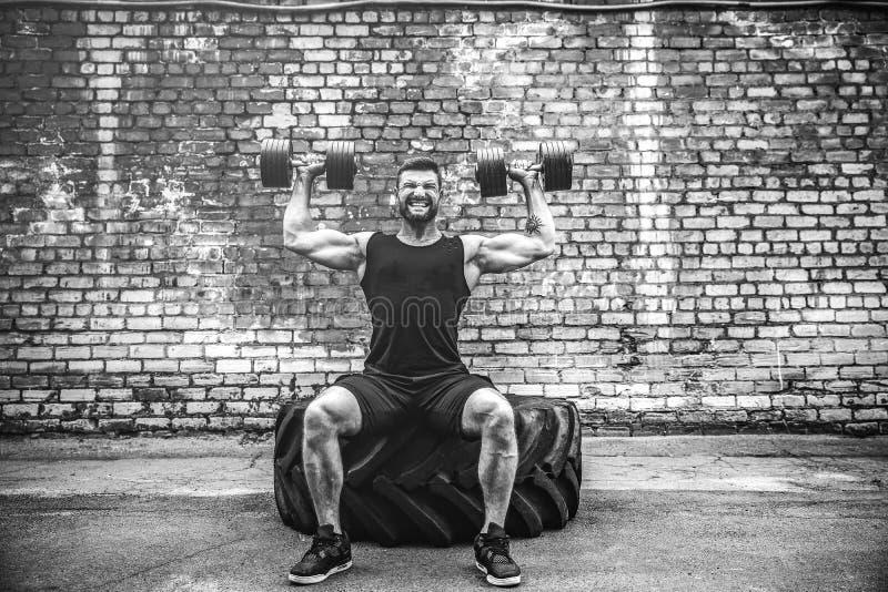 Мышечный парень делая тренировки с гантелью против кирпичной стены стоковое изображение