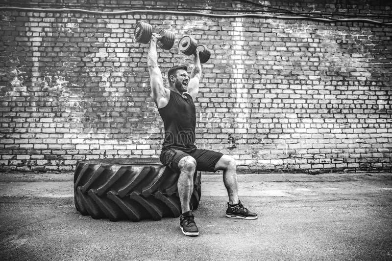 Мышечный парень делая тренировки с гантелью против кирпичной стены стоковые фото