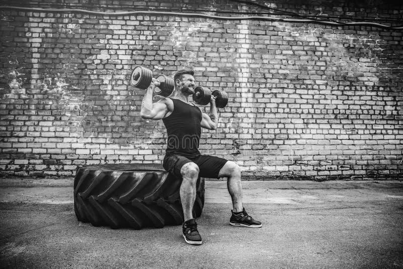 Мышечный парень делая тренировки с гантелью против кирпичной стены стоковые изображения rf