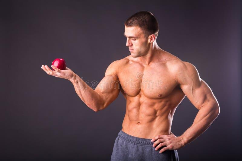 Мышечный парень держа яблоко и грушу стоковые изображения rf